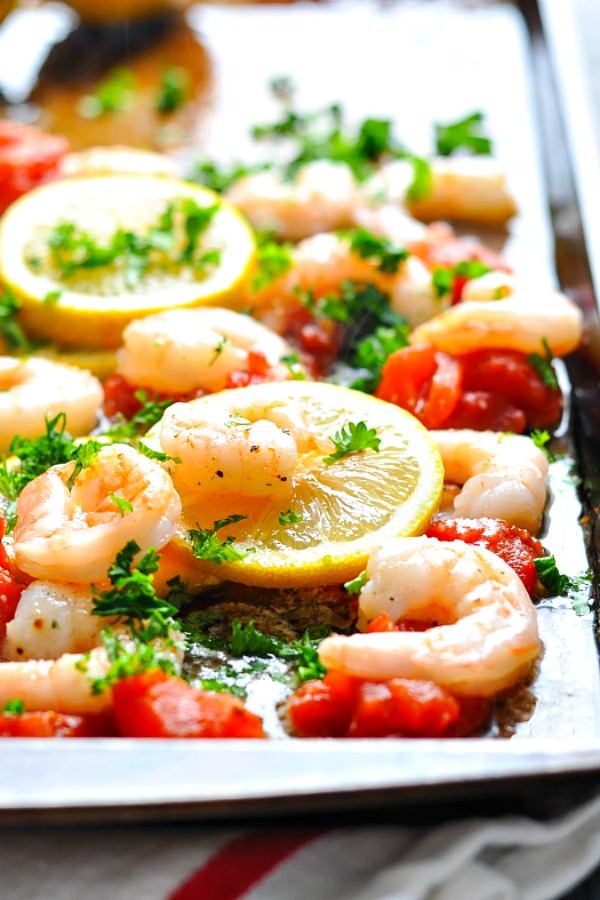 Close shot of Italian Baked Shrimp with tomatoes on a sheet pan garnished with fresh parsley