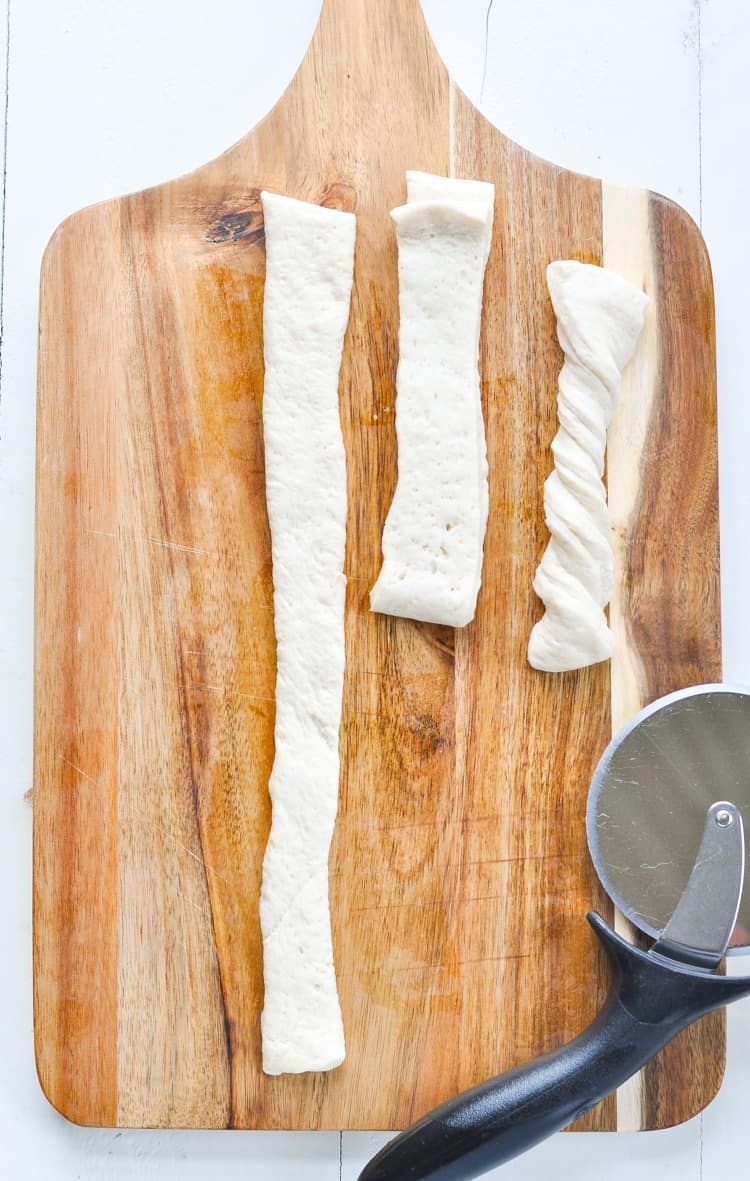 Overhead image of breadstick dough on a cutting board