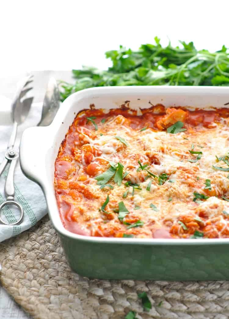 Close up photograph of a casserole dish with baked gnocchi and chicken that's topped with melted cheese and fresh herbs.