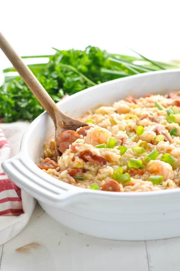 Baked Jambalaya in a white casserole dish with wooden serving spoon