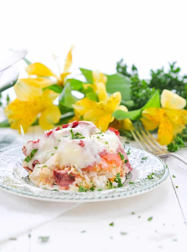 A serving of Reuben Casserole on a plate with yellow flowers in the background