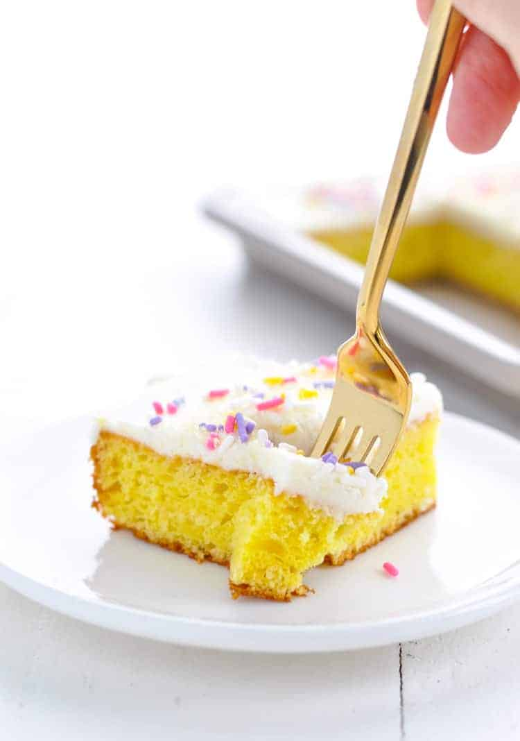 A square of frosted lemon bar with sprinkles on a plate with a fork.