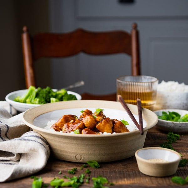 Side square shot of the best general tso chicken recipe in a bowl with chopsticks