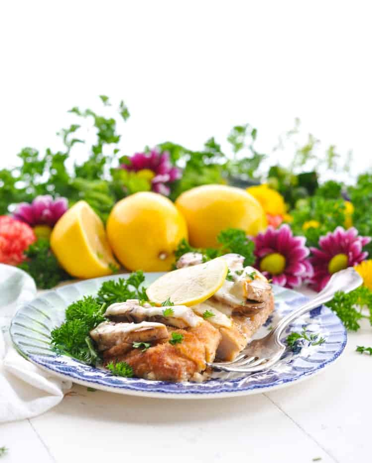 Baked chicken breast on a plate with lemons and flowers in the background.