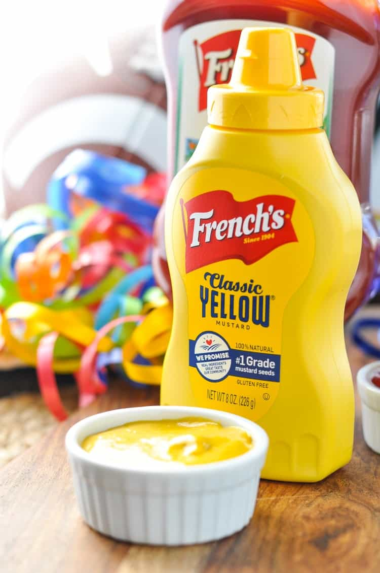 Bottle of French's mustard sitting on a wooden surface sued for dipping pretzel dogs into