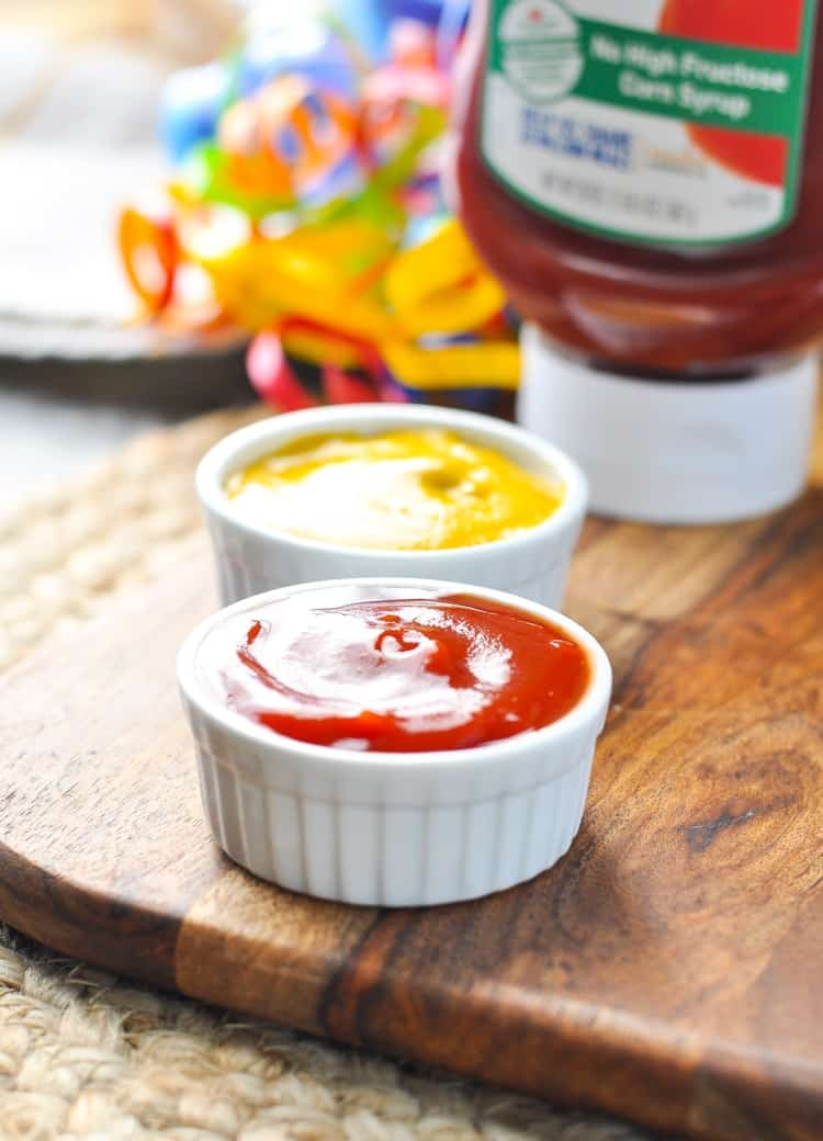 Ketchup and mustard dips in ramekins sitting on a wooden board