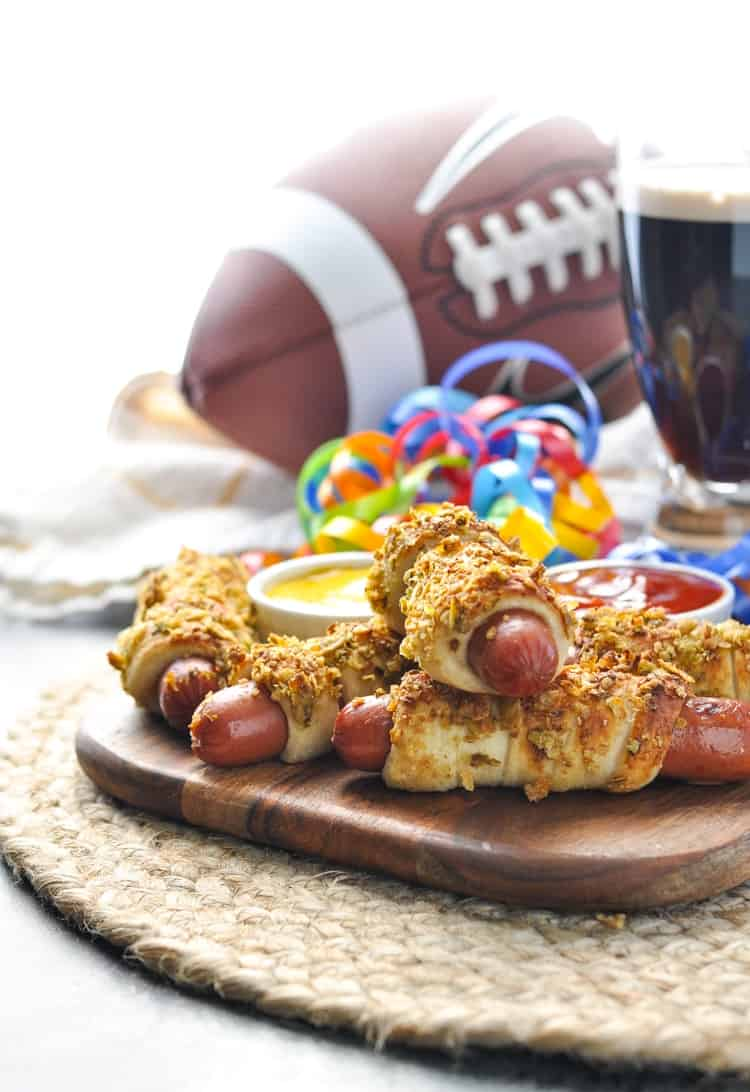 A pile of Jalapeno Pretzel Dogs with a beer and football in the background