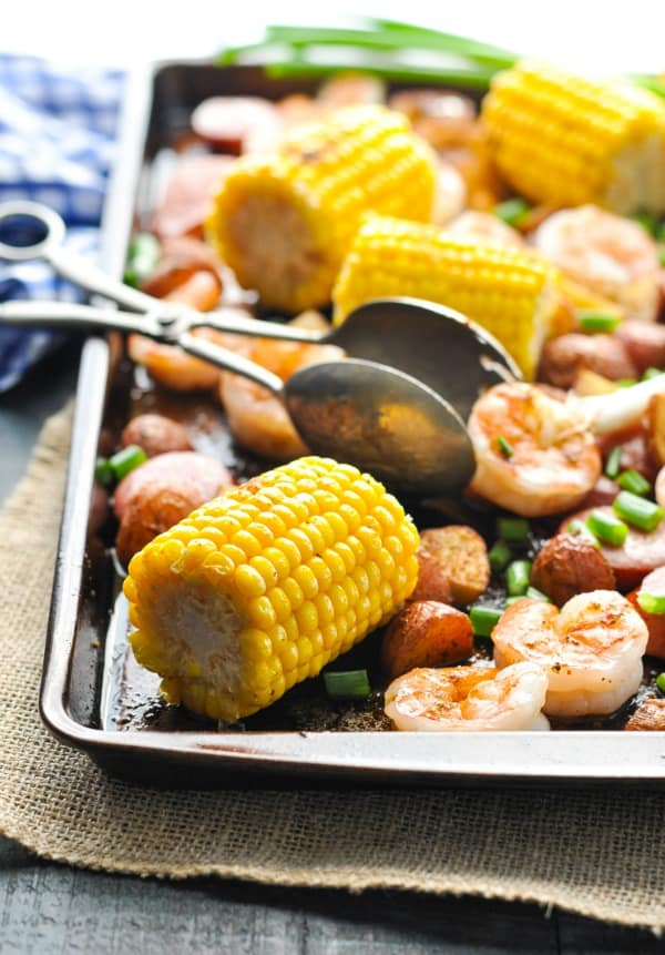 Sheet Pan Low Country Boil with shrimp and sausage on a platter with serving tongs