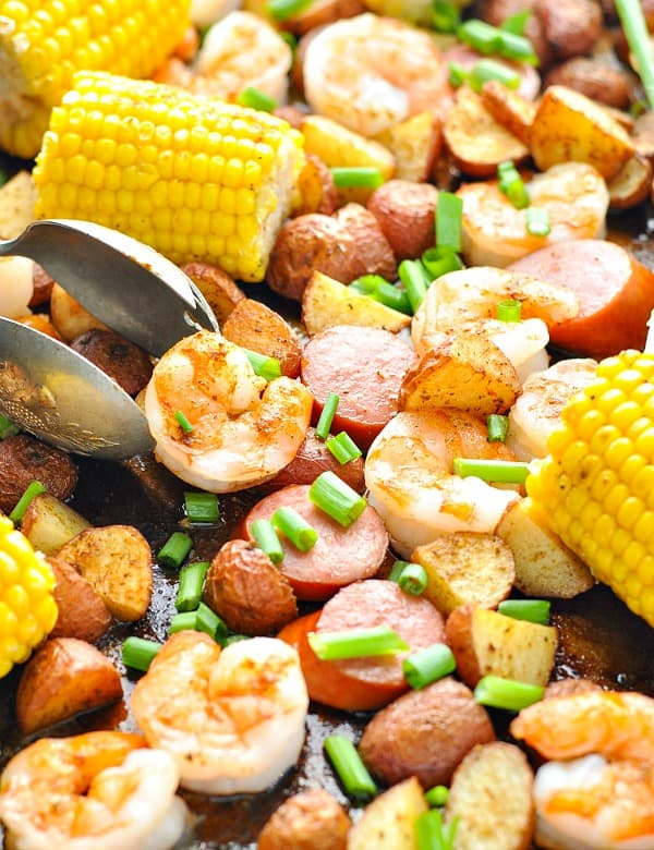 Close up shot of low country boil from the oven on a baking sheet with serving tongs