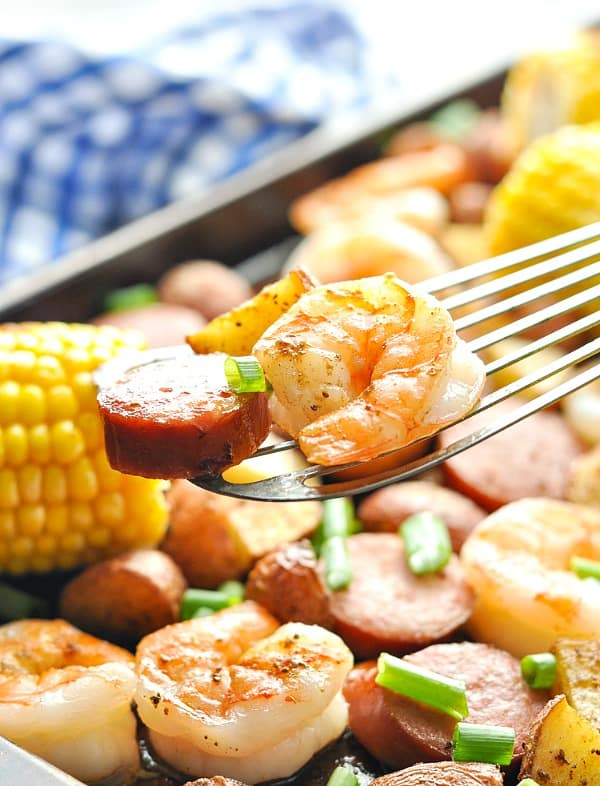 Close up shot of spatula picking up shrimp and sausage from low country boil sheet pan supper
