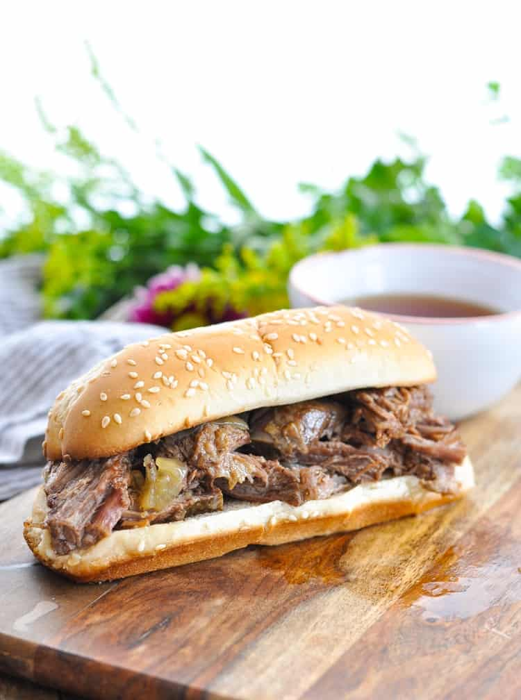 Photo of easy slow cooker French Dip Sandwiches on a wooden board
