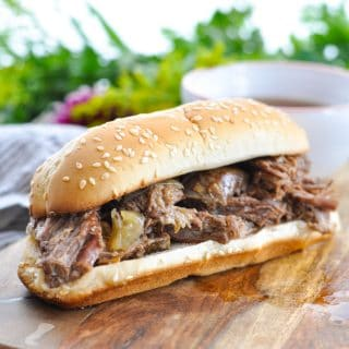 Photo of easy slow cooker French Dip Sandwiches on a wooden board with dipping sauce in the background