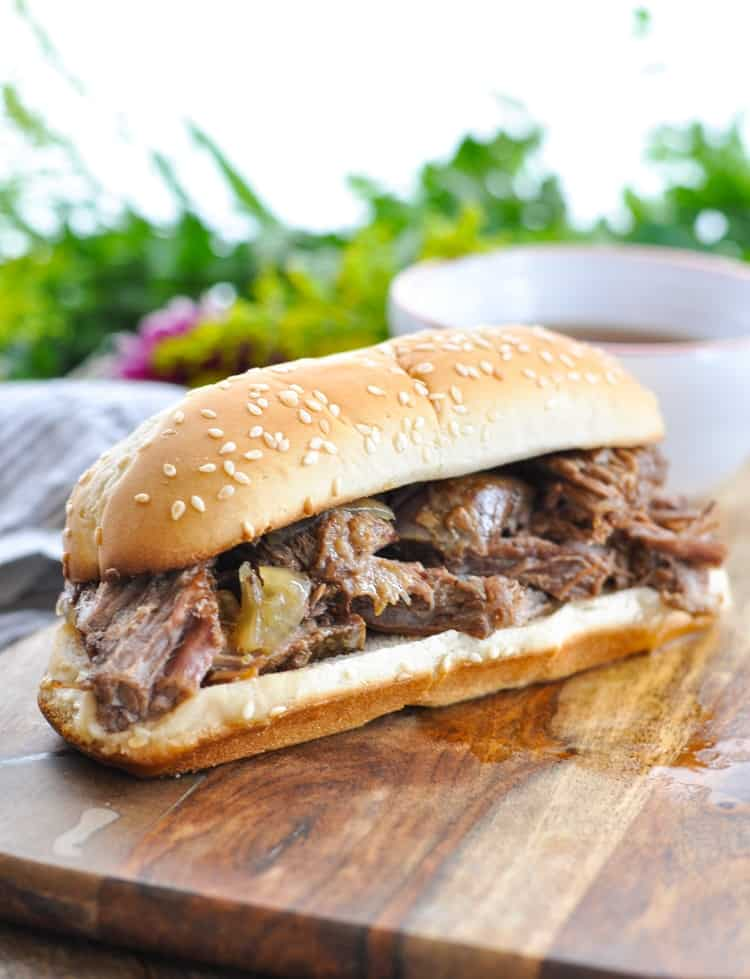 A close up of slow cooker french dip sandwiches on a wooden board