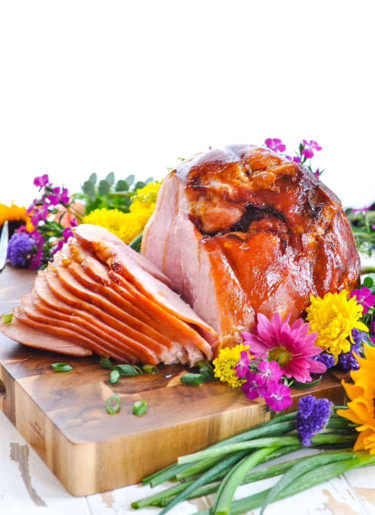 Sliced baked and glazed ham on a cutting board that's perfect for a holiday dinner