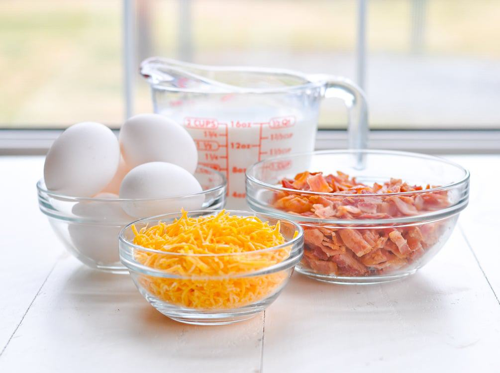 Ingredients for making a breakfast casserole with bacon and cheese