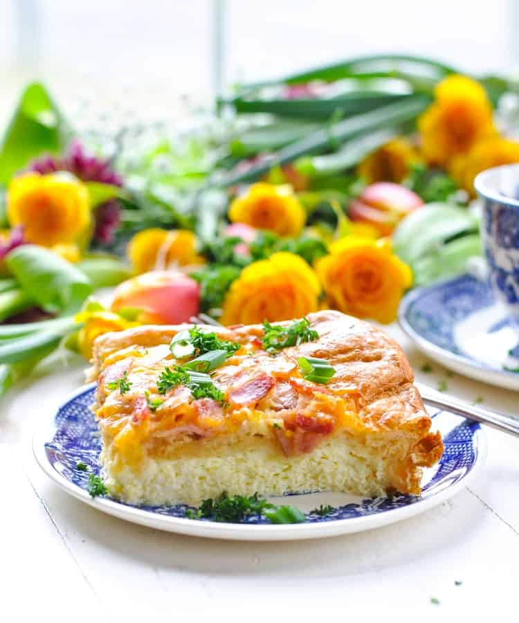 A close up of a breakfast casserole with bacon on a small blue plate with flowers in the background
