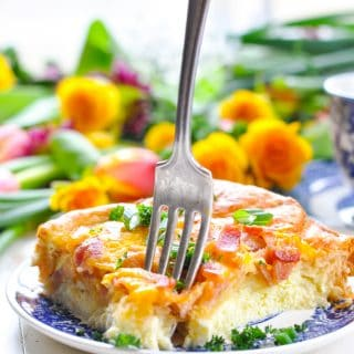 A close up of a breakfast casserole with bacon on a small plate