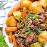 Long overhead image of a plate of a chuck roast recipe surrounded by potatoes and carrots