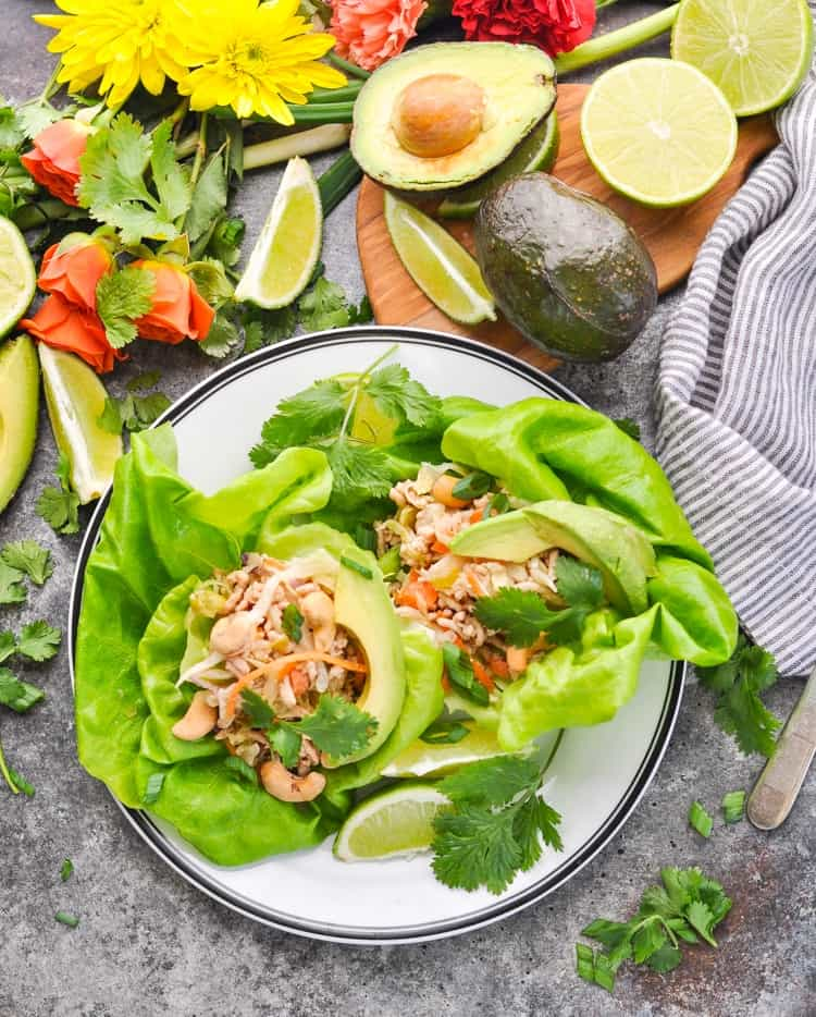Asian Turkey Lettuce wraps garnished with avocado and cashews on a plate for a healthy dinner recipe in minutes!