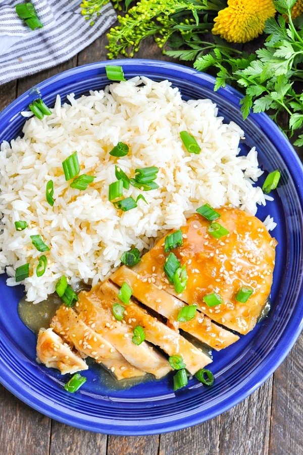 Overhead shot of baked bourbon chicken on a blue plate with rice and green onions