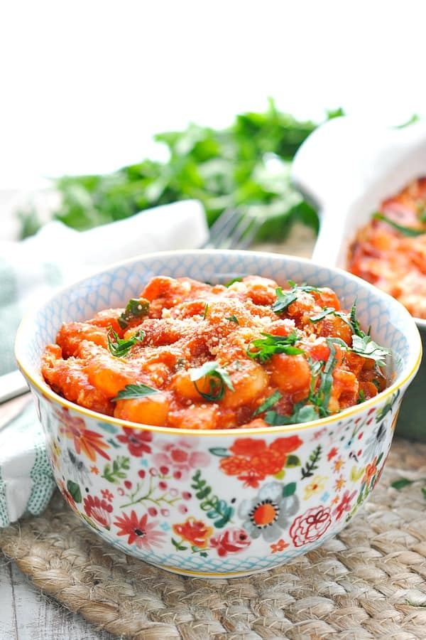 Close up shot of chicken marinara gnocchi recipe in a colorful bowl with fresh parsley on top