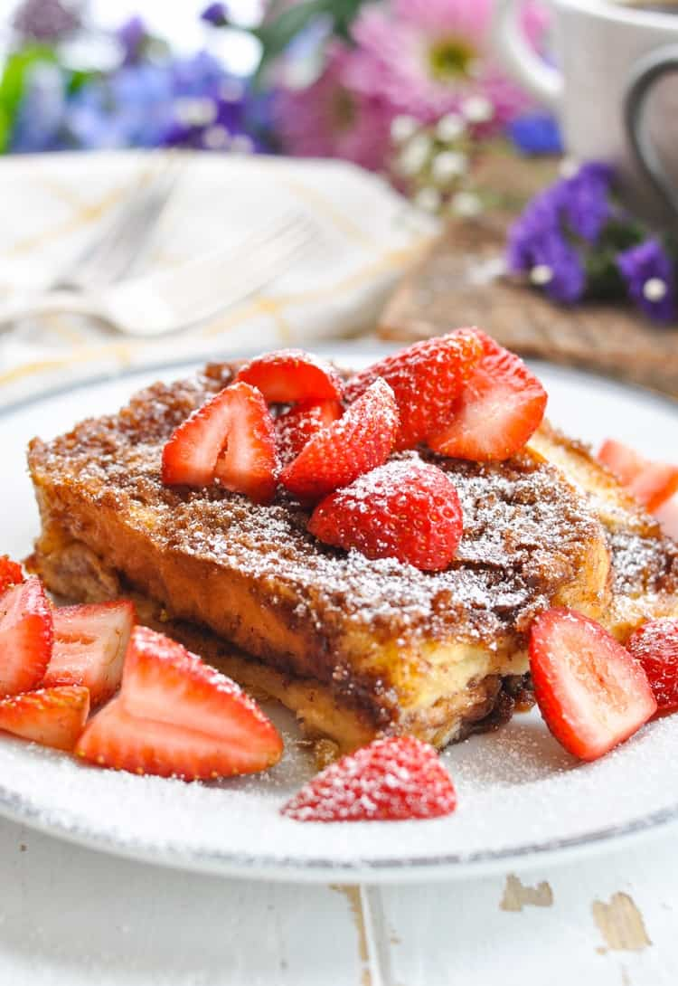 A close up shot of an easy French Toast casserole on a plate topped with powdered sugar and strawberries