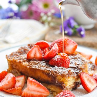 A close up of an easy french toast casserole on a plate topped with berries