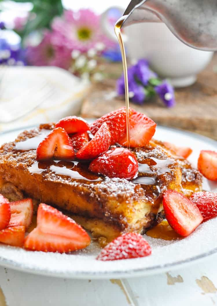 A photo of a slice of an easy french toast casserole sitting on a plate topped with strawberries and maple syrup