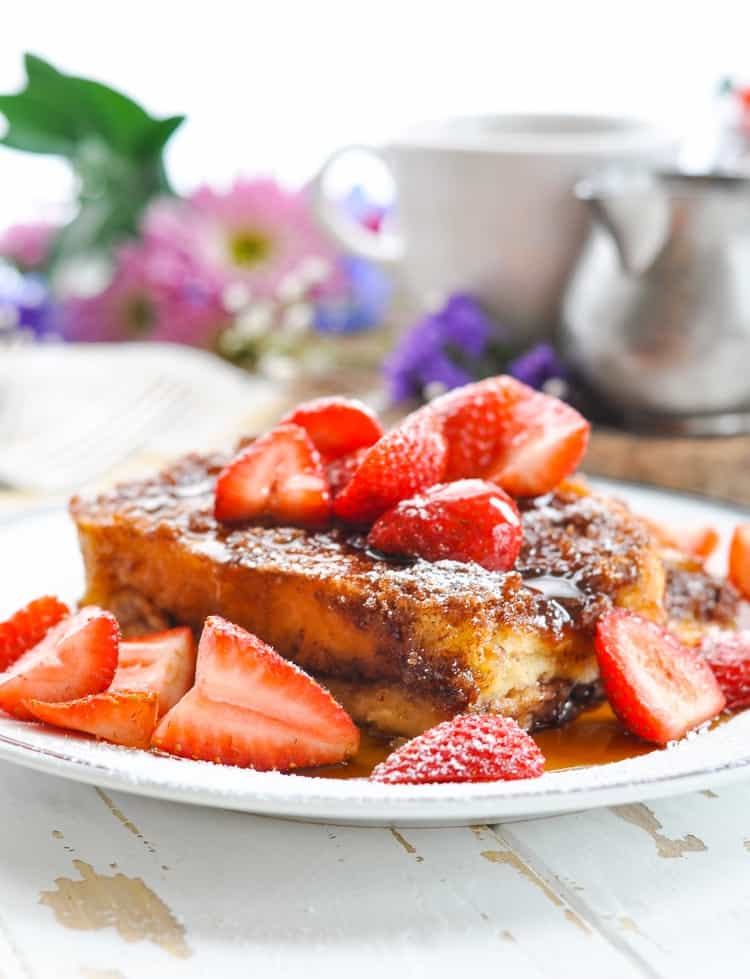 A slice of Dump and Bake Easy French Toast Casserole on a plate with berries and maple syrup