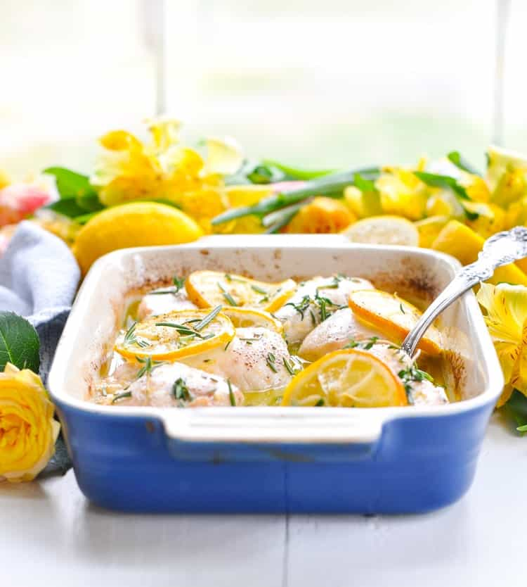 A healthy dinner of baked lemon chicken breasts in a white wine sauce in a blue casserole dish