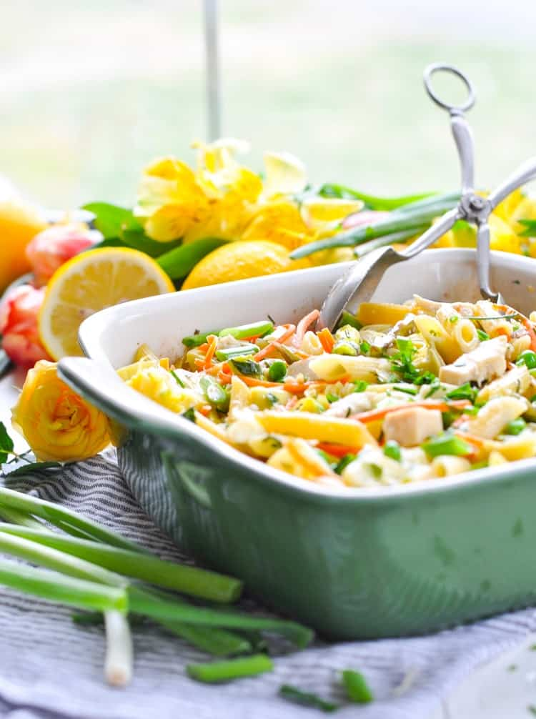 A spring pasta casserole with chicken, artichokes, carrots, peas, and chives.