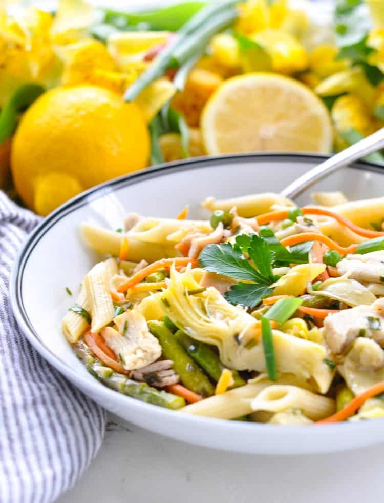 A pasta bowl full of spring vegetables like artichokes, asparagus, and peas with chicken and pasta.