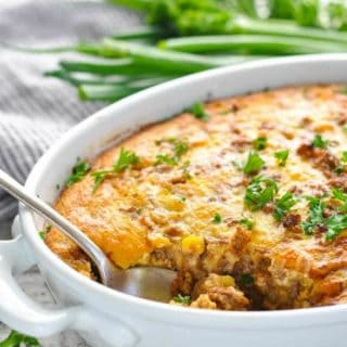 Cheeseburger Pie in a white casserole dish garnished with fresh parsley
