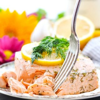 Close up shot of a fork taking a piece of poached salmon