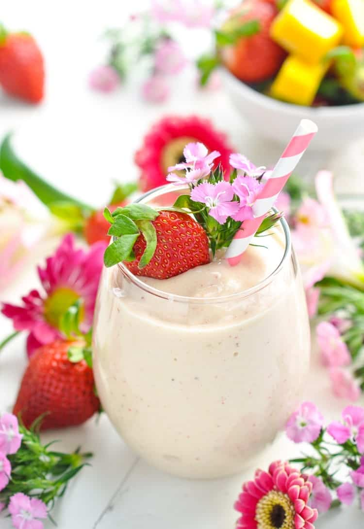 Bright image of pink flowers fresh strawberries and a Healthy Strawberry Smoothie