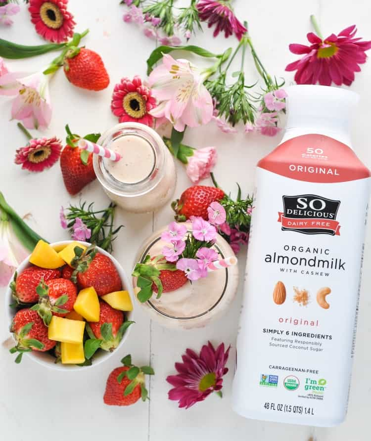 Overhead image of Strawberry Smoothie with bottle of almondmilk and fresh fruit and flowers