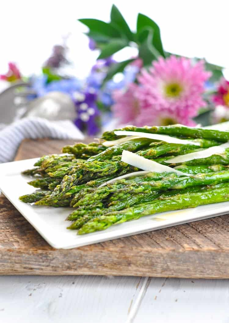 Asparagus with shaved Parmesan on a platter with flowers