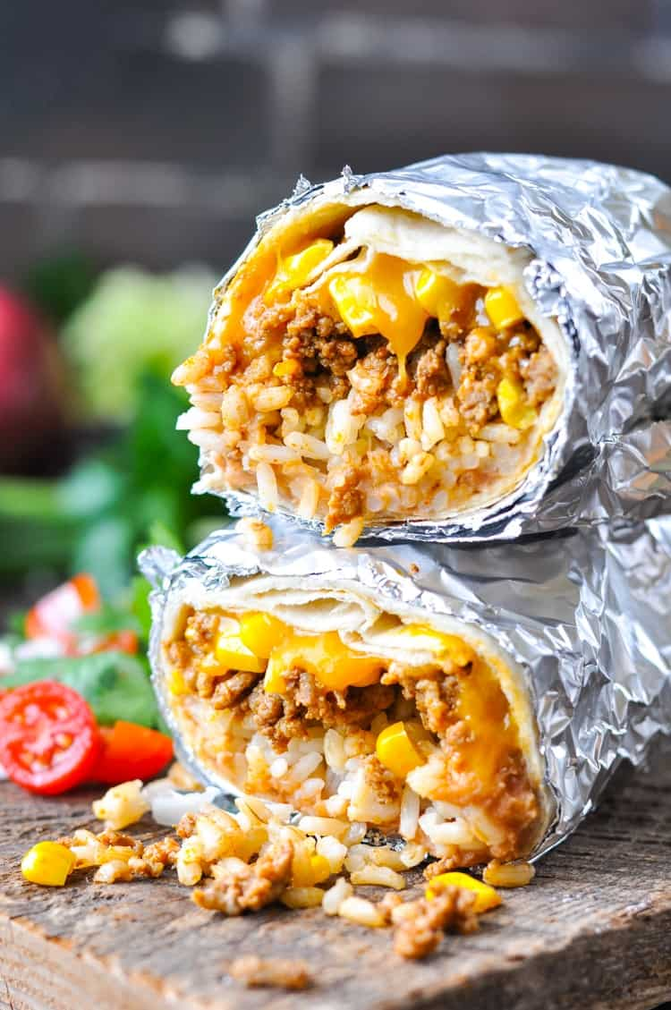 Stacked beef burritos on a board with melted cheese