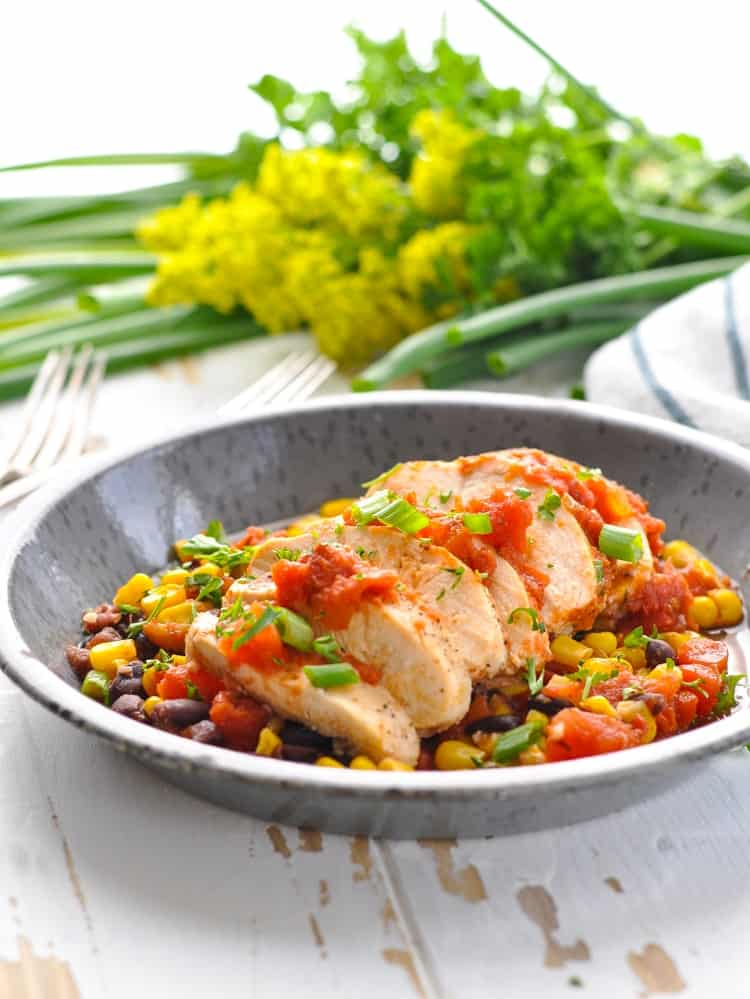Sliced chicken breasts on a plate with corn and black bean salsa for a healthy dinner