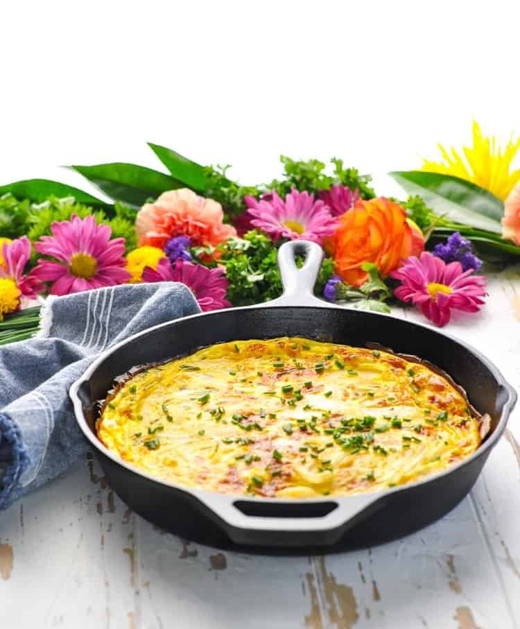 Crustless quiche or easy frittata in a cast iron skillet sitting on a white wooden surface