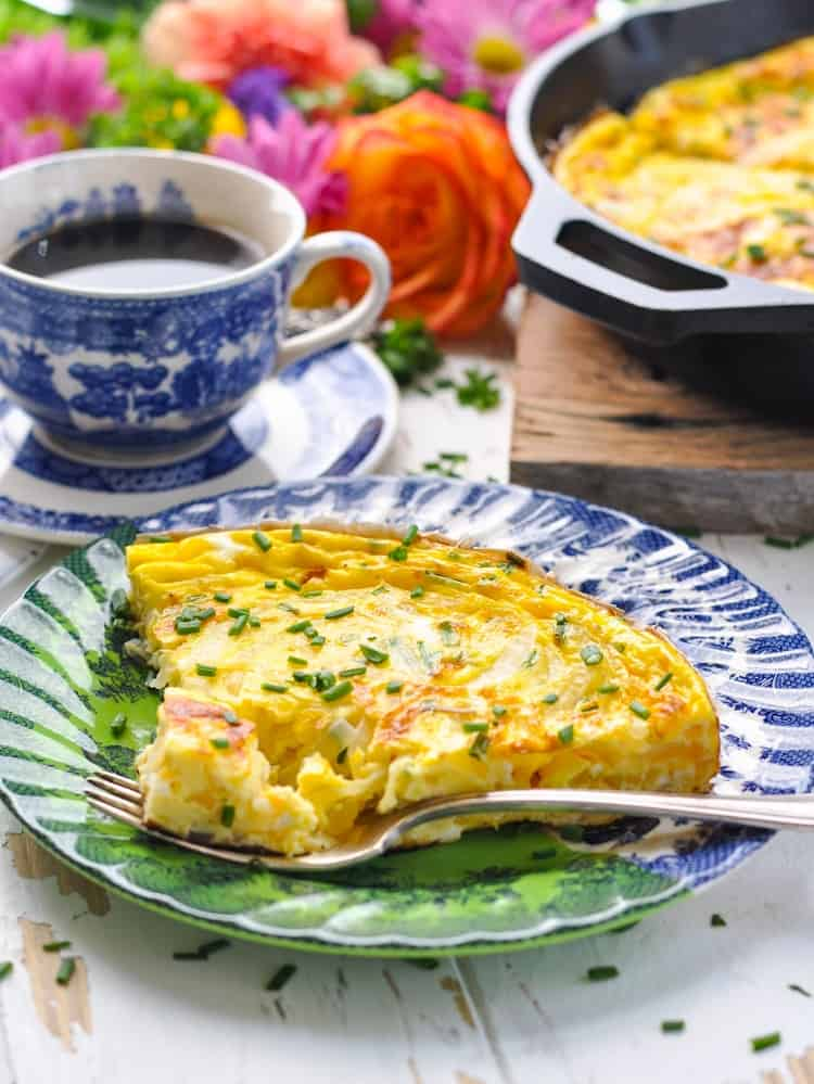 A photo of a slice of easy frittata made with cheddar cheese and chives on a blue plate with a cup of coffee in the background