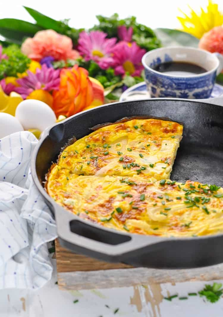 A photo of an easy frittata in a cast iron skillet with a slice taken out