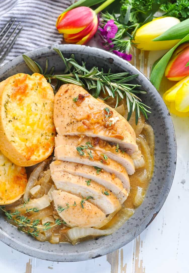 Close overhead image of baked French Onion Chicken in a bowl with cheese toast