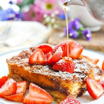 Slice of Easy French Toast Casserole on a white plate topped with fresh strawberries and pour of maple syrup