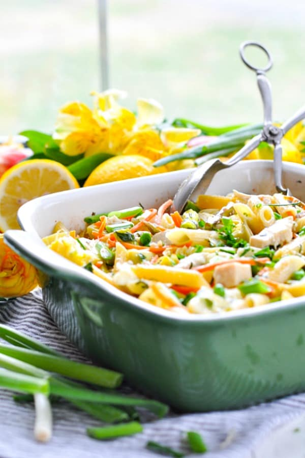 A healthy baked pasta dish with spring vegetables in a green casserole dish