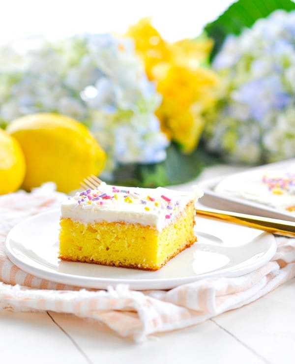 Frosted Lemon Bar on a white plate with flowers in background