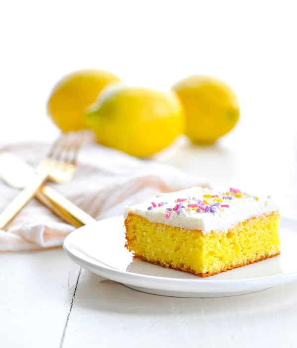 Lemon bar on a plate with lemons in the background