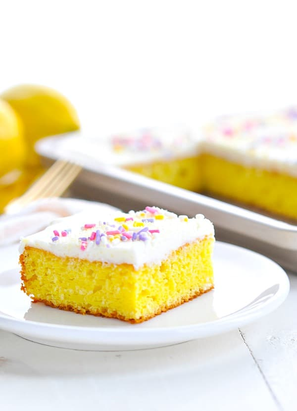 Frosted Lemon bar on a white plate with pastel sprinkles