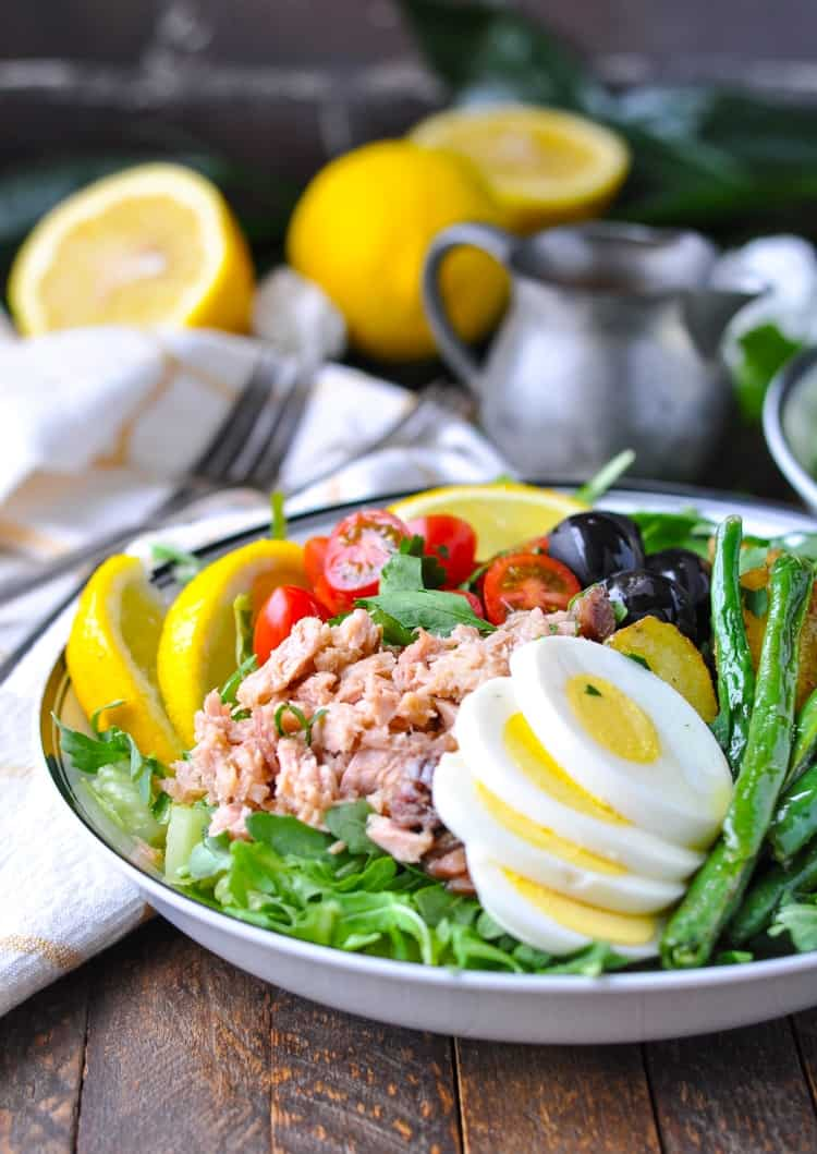 A side shot of a Tuna Nicoise Salad on a wooden surface