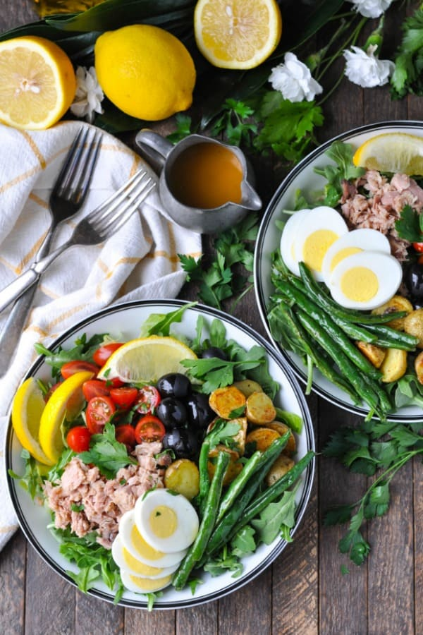 An overhead shot of tuna nicoise salad bowls on a wooden surface with a vinaigrette at the side